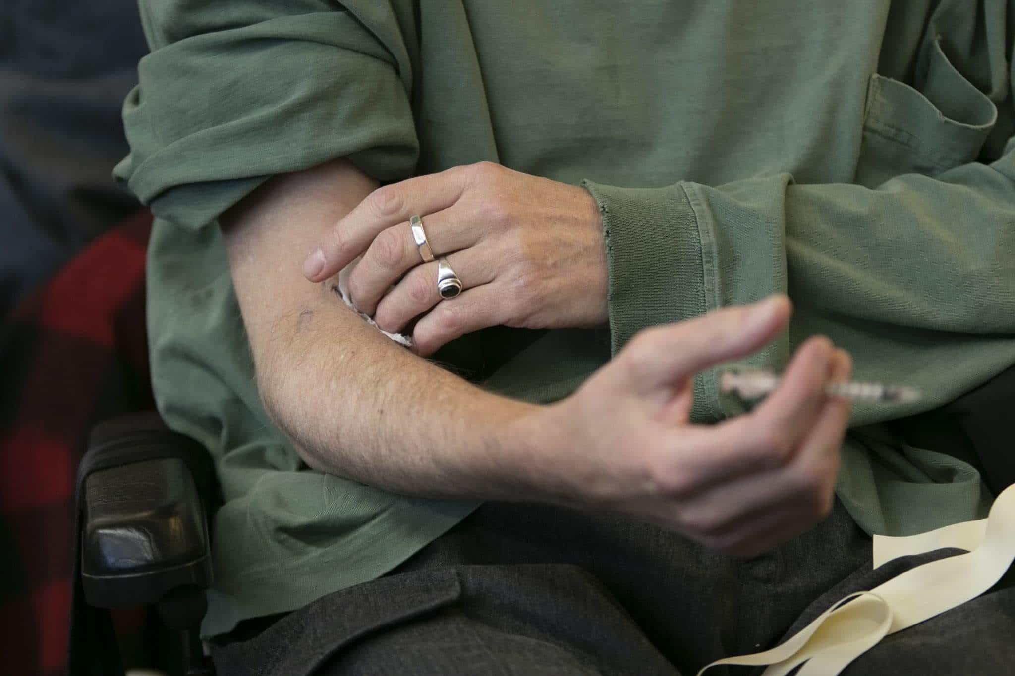 Hand pressing cotton pad on arm that is holding a syringe