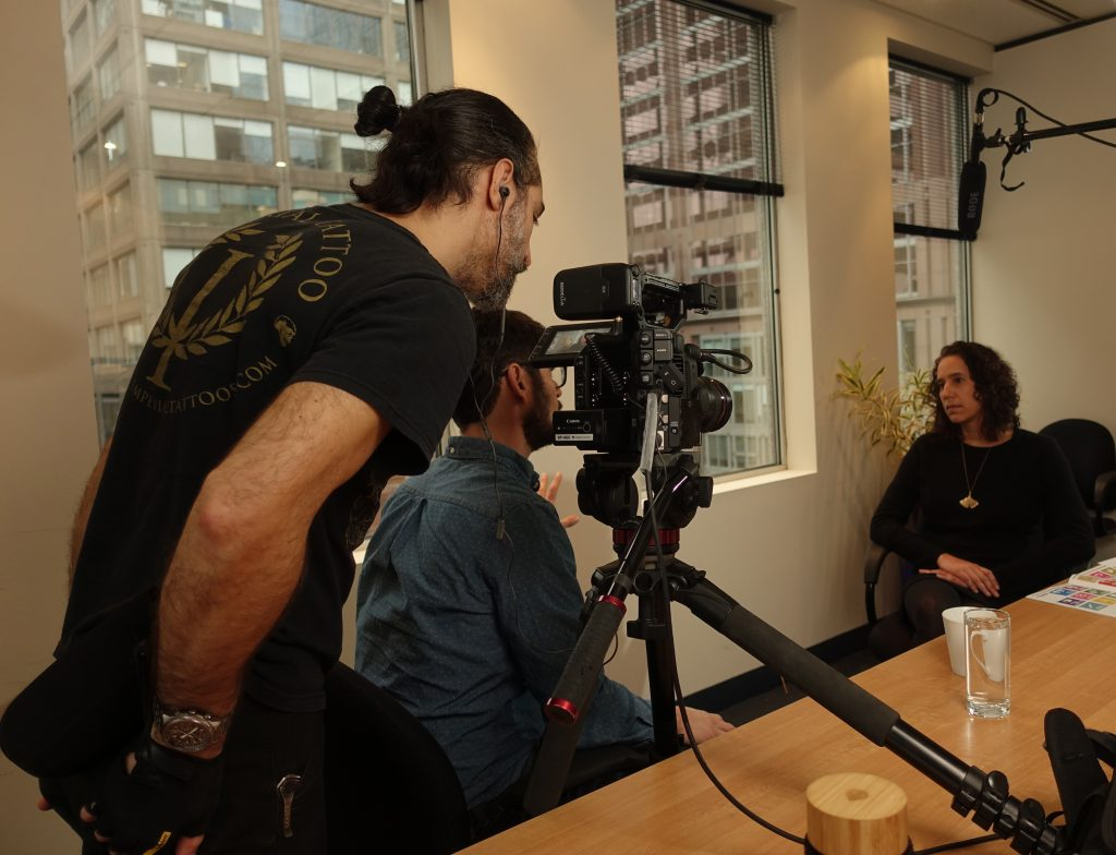 woman sits at a desk being interviewed by a camera crew