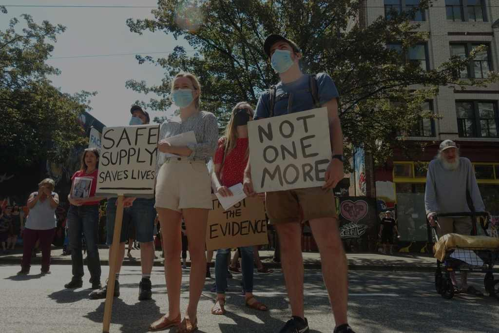 three people holding up signs at the safe supply rally in Vancouver, 2020