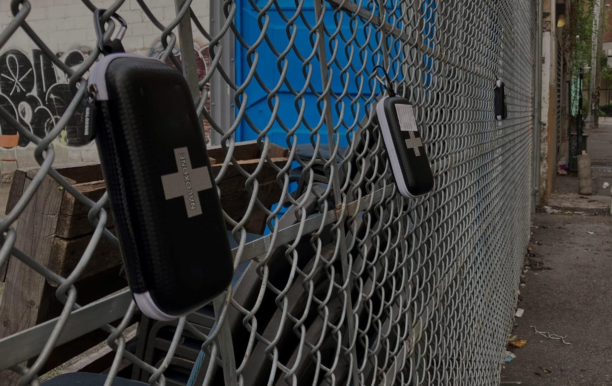 Three naloxone kits strung up to a chain link fence