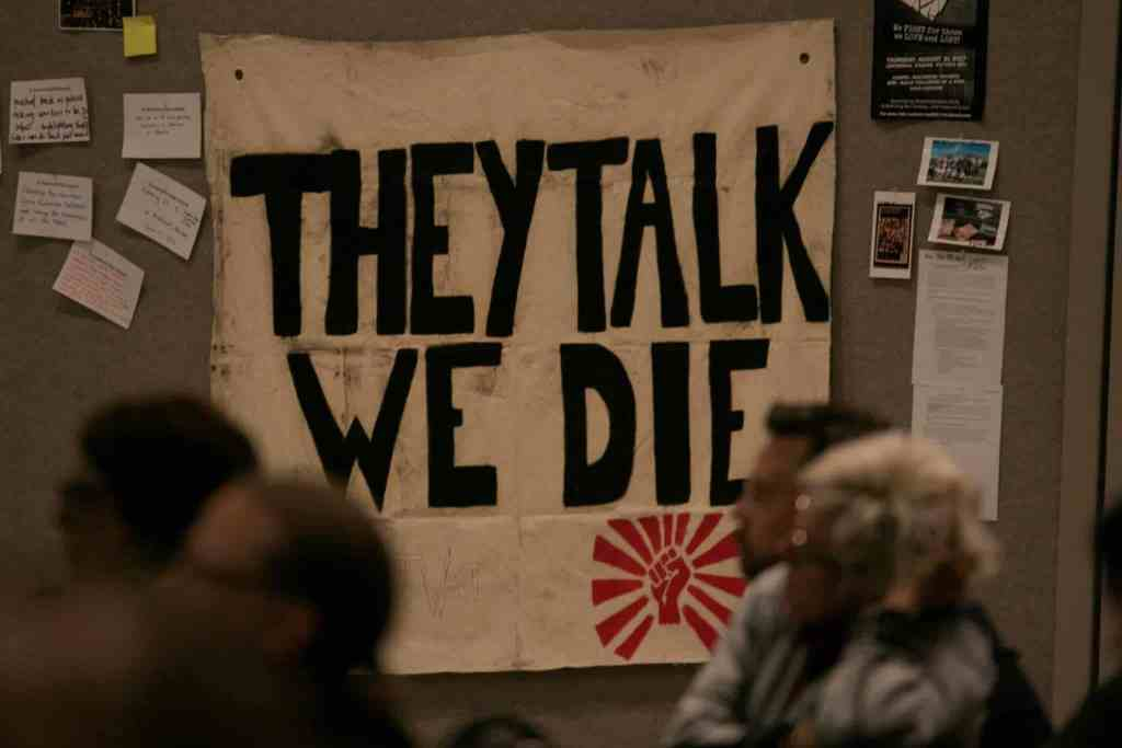 """Banner with the phrase, """"they talk we die"""" written on it"""