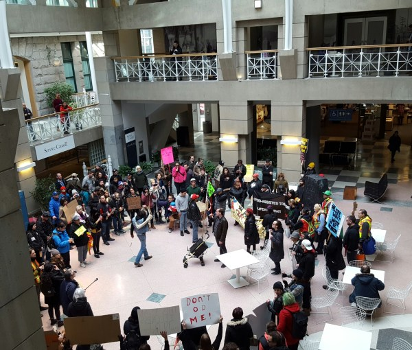 Crowd of people standing in an atrium holding protest signs   Getting to tomorrow