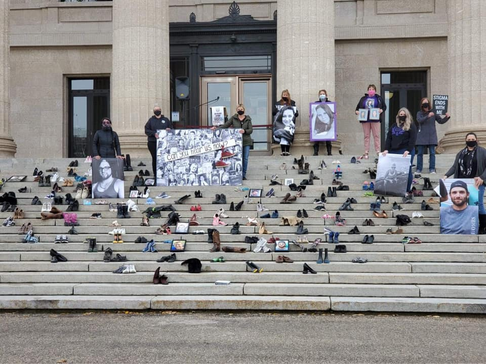 Shoes on the steps of a building in front of a row of family members holding photos of their loved ones