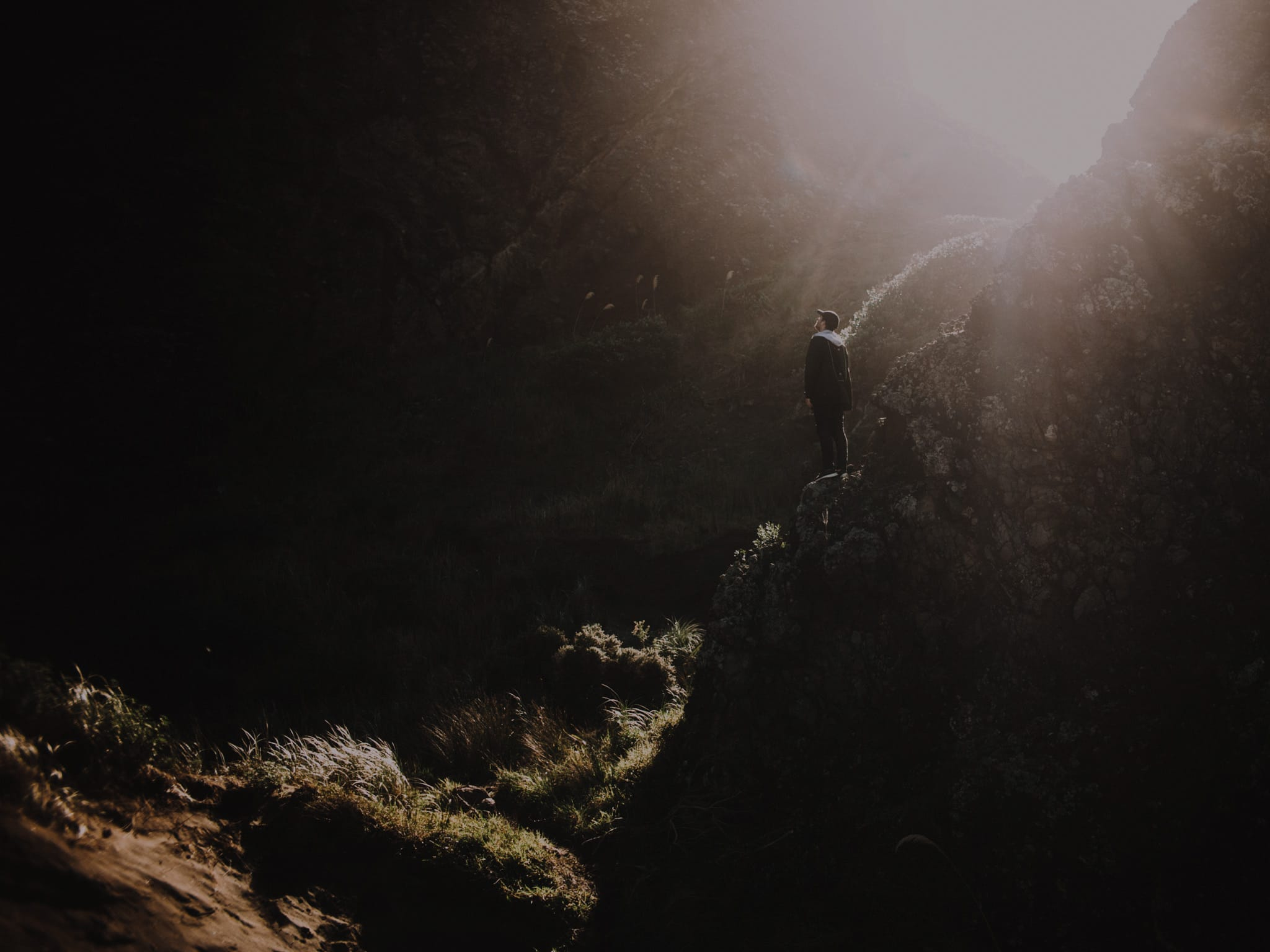 Man standing on a rock outcrop in a dark cave witha ray of light shine from above.