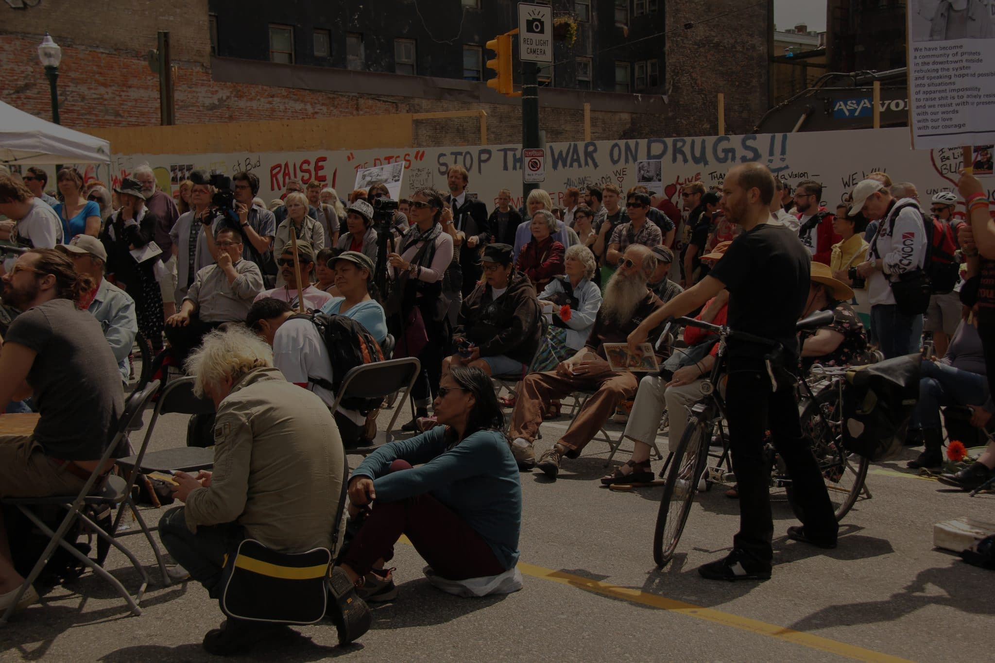 A crowd listening to a speaker at a rally in the Downtown Eastside