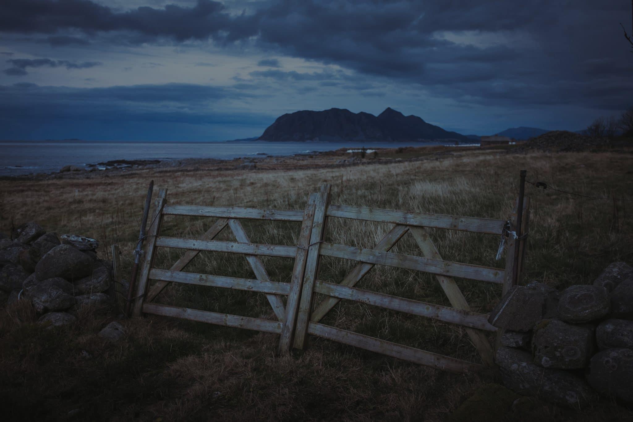 A broken fence serving as a barrier to a field