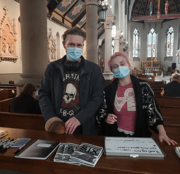 A man and a woman standing at a display table in a church