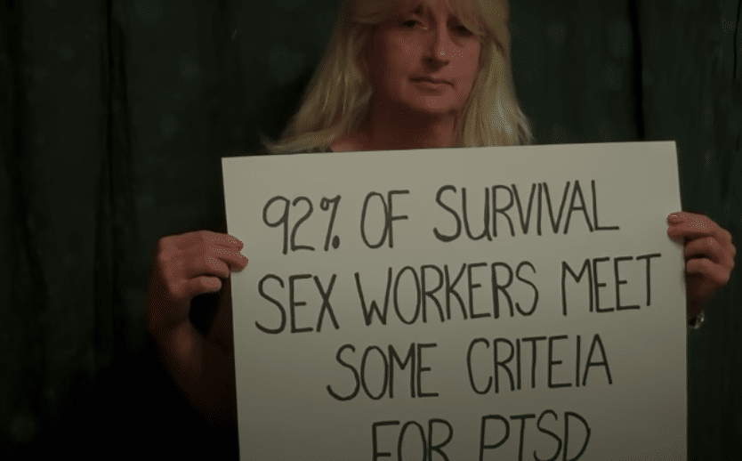 A women holding a sign with text