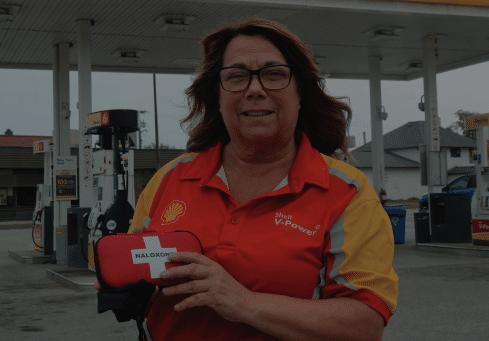 Female gas station attendant holding a Naloxone case
